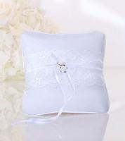 Weißes Ringkissen mit Spitzenband und weißen Blüten